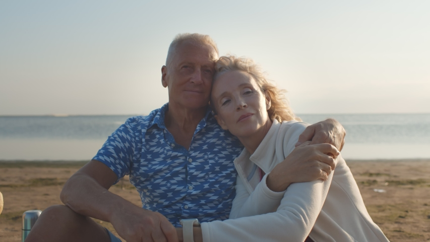 Loving senior couple hugging sitting on sea beach outdoor. Happy elderly man and woman enjoying retirement and life. Concept of wellbeing, happiness, male and female health, tenderness. Royalty-Free Stock Footage #1055411801