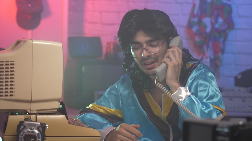 Cheesy looking young man from the 80s 90s taking a call on a land phone. Vintage background and clothing simulating the 1980 1990 era. | Shutterstock HD Video #1055412632