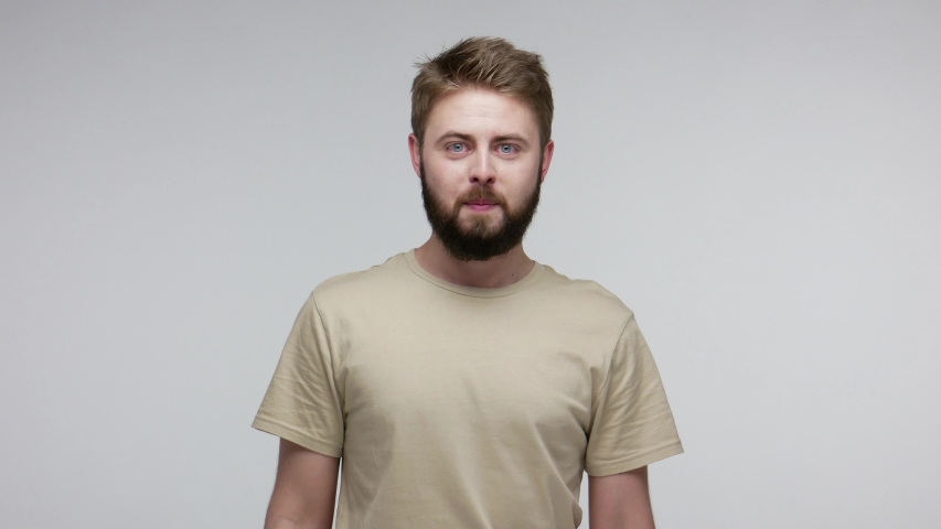 Funny crazy uncultured bearded man picking dirty nose, pulling out boogers and throwing disgusting mucus at camera, bad manners, ugly misconduct concept. indoor studio shot isolated on gray background