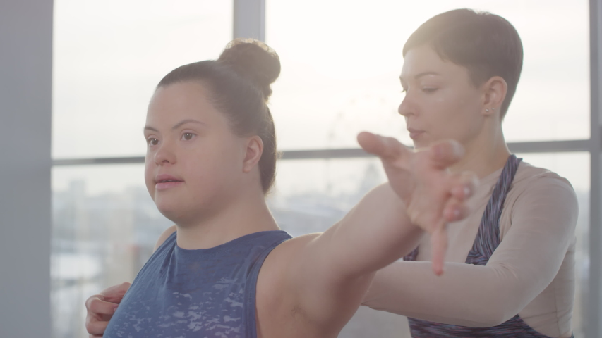 Cheerful young disabled woman with down syndrome doing yoga exercise with her personal trainer helping her Royalty-Free Stock Footage #1055414384
