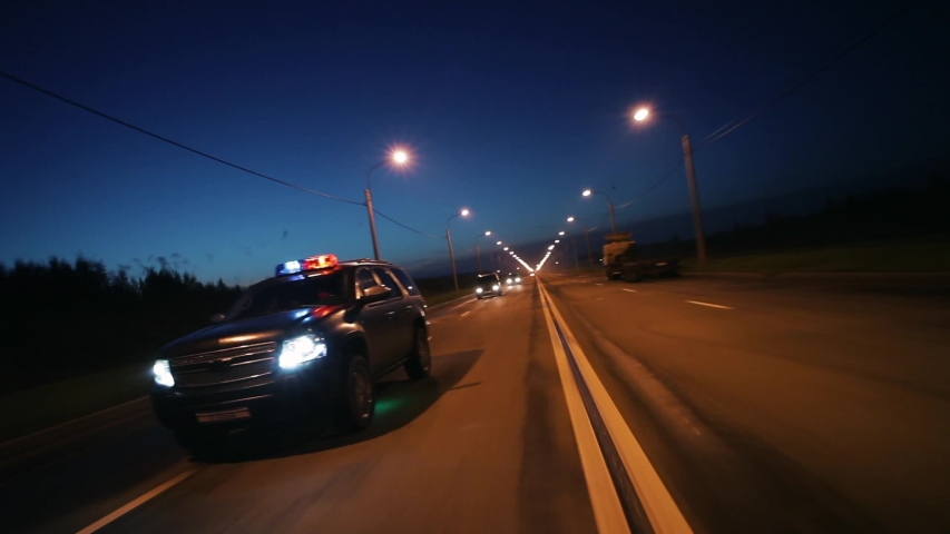 Cop car in high speed pursuit. Emergency response police patrol vehicle speeding to scene of crime. Outdoor front view of police traffic auto driving. Car active driving. Flashers. | Shutterstock HD Video #1055415536
