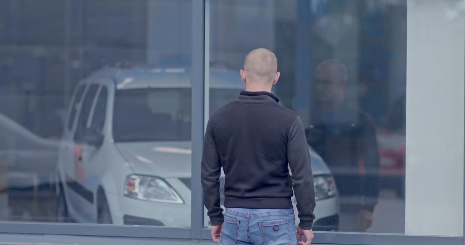 Showcase car dealership with cars. Sale of a cars at a luxury car dealership. Man looks through the window of a car dealership, chooses a new car. View from the back. | Shutterstock HD Video #1055417444