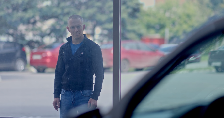 Young man looks at the car through the showcase of a car dealership. Buying a car, a man chooses a car. Portrait view.