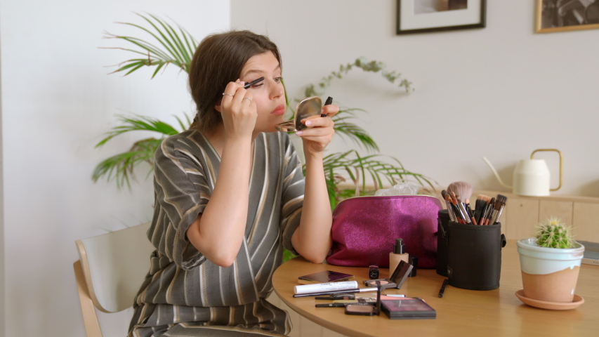 Confident happy young woman holding mascara apply on eyelashes. Preparing to go out. Beautiful girl doing make up put cosmetics on face looking in mirror at home. Makeup routine at the morning | Shutterstock HD Video #1055418335