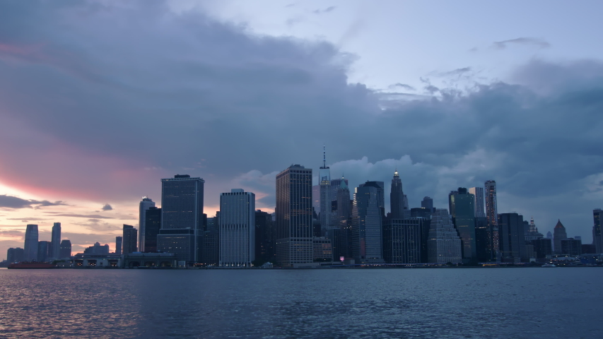 Timelapse of summer clouds flying over Downtown Manhattan skyline, twilight into night, as seen across the East river from Brooklyn summer 2020 | Shutterstock HD Video #1055418872
