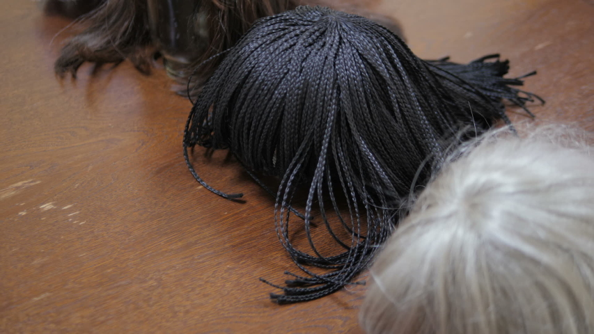 Artificial hair. Wir on table. Hairdressers room. Wooden table. Brown wig. Grey wig. Black wig. Hairstyle cut. Head hair style. Beautiful wig. Hair salon. Hairdressing saloon. Barber shop. Stylist | Shutterstock HD Video #1055419598