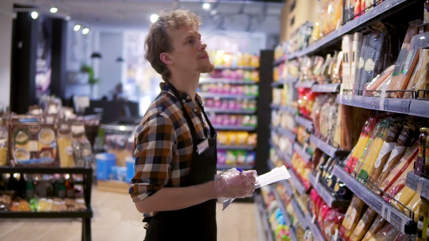 Serious store clerk working at the supermarket he is resorting items on a shelf, writing down the lack of products down on the pad. Side view   Shutterstock HD Video #1055430071