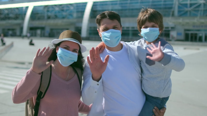 Happy family tourists mother, father, son little boy child in airport in protective medical face mask. Virus outbreak Coronavirus COVID-19 flu quarantine pandemic. Safe travel tourism kid. slow-mo 4 K Royalty-Free Stock Footage #1055433629
