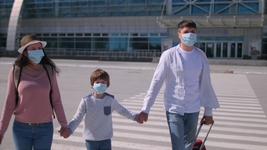 Happy family tourists mother, father, son little boy child in airport in protective medical face mask. Virus outbreak Coronavirus COVID-19 flu quarantine pandemic. Safe travel tourism kid. slow-mo 4 K Royalty-Free Stock Footage #1055433641