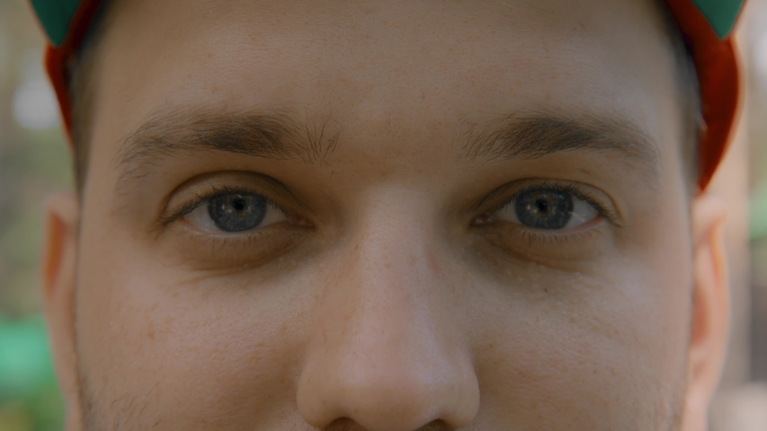 Close-up portrait of a young man. Blue eyes of a young guy close-up, natural beauty. The young guy looks at the camera, blinks, and smiles. Full-face view. Warm color, slow motion. 4K | Shutterstock HD Video #1055434184