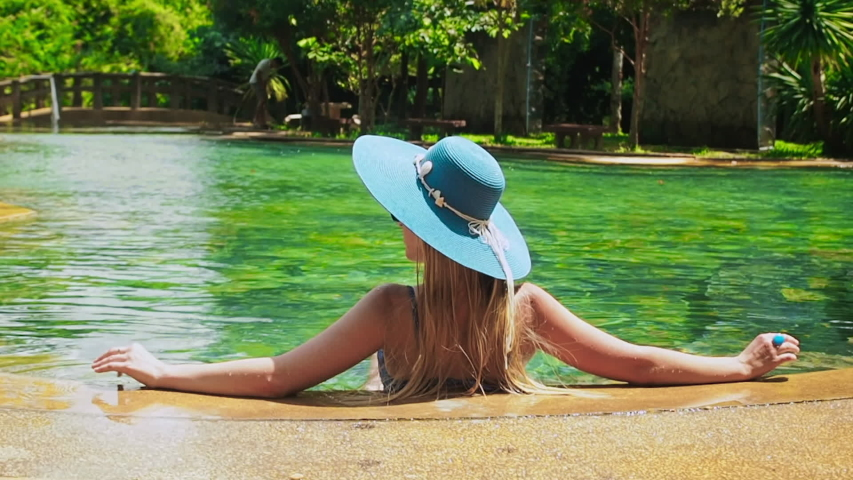 Pretty lady in a blue swimsuit, hat and sunglasses sits and relaxes in tropical swimming pool with clear water on a sunny day back view. Woman straightens the hat in green water of tropical pool | Shutterstock HD Video #1055434640
