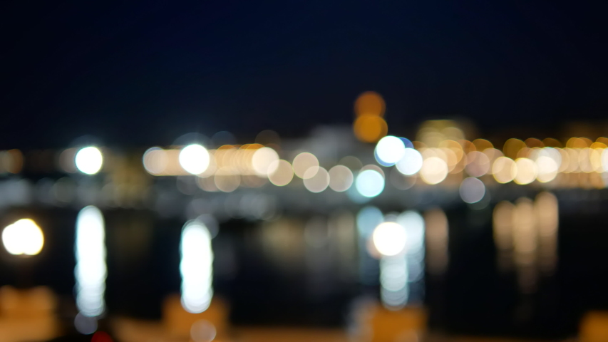 Blurred evening lights and water background in Bari in Italy. Handheld.