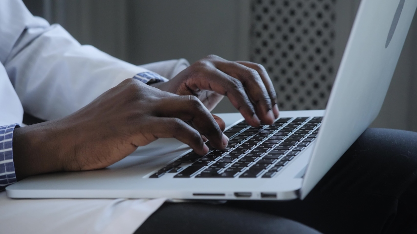 Male african american user hands typing on laptop keyboard sit at table, mixed race ethnic student professional study work with pc software technology concept, close up view | Shutterstock HD Video #1055435939