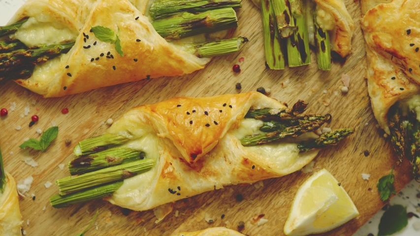Grilled green asparagus and cheese puff pastry folded as envelope and topped with black sesame seeds placed on wooden cutting board. Top view, flat lay.