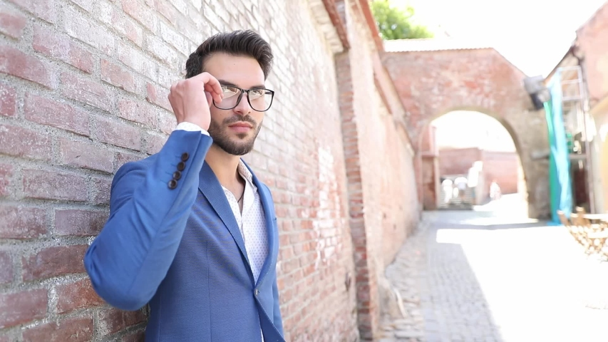 Cool businessman leaning on a brick wall, removing his glasses from his eyes, laughing out loud and holding a briefcase | Shutterstock HD Video #1055440235