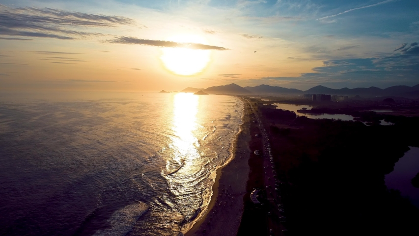 Rio de Janeiro, Brazil: Aerial Landscape of Tropical Sunset on Beach. Vacations. Vacation Travel. Travel Destination. Tropical View. Seaside. Aerial Landscape. Barra da Tijuca, Rio de Janeiro. Sunset. | Shutterstock HD Video #1055442071