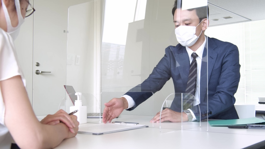 People meeting across an acrylic partitions. Infection prevention. Royalty-Free Stock Footage #1055444042