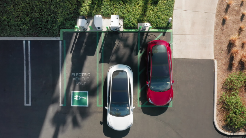 4K aerial overhead view on white electric vehicle parking at the charging station. Slow motion footage with environmental and eco-friendly, zero pollution technology concept. Royalty-Free Stock Footage #1055446742