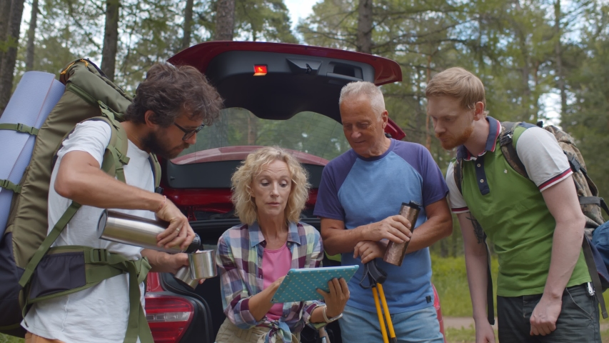 Happy family near car using tablet pc looking for location in woods. Senior parents and adult children planning traveling route on digital tablet standing near open car in forest