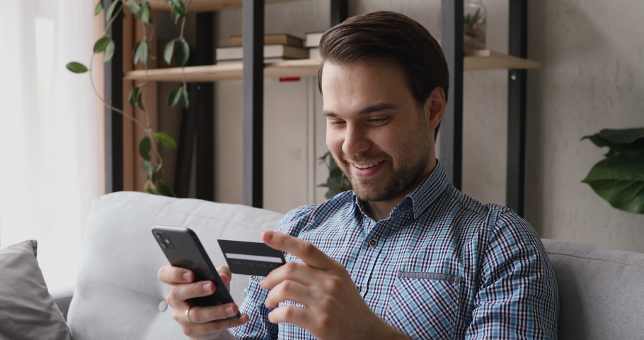 Smiling man sitting on couch holding cellphone using credit card makes instant payment feels happy. Easy on-line shopping, modern tech, safe successful convenient payment, sale and discounts concept Royalty-Free Stock Footage #1055448761