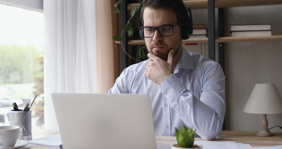 Serious man wear headset look ap pc screen writes ideas questions do review make research sit at desk. Businessman learn language improve knowledge, self-education, modern tech educational app concept Royalty-Free Stock Footage #1055448764
