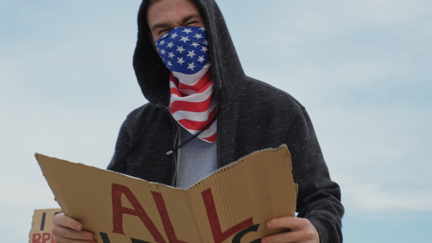 Young man solitary street protests stands with sign All Lives Matter on cardboard in hands background of blue sky at sunset summer. Black Lives Matter. Freedom consept. Riots wold Royalty-Free Stock Footage #1055450438