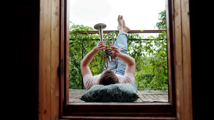 a happy man plays the trumpet on the balcony. feet up free time for a favorite activity in the midst of a coronavirus pandemic and social distancing Royalty-Free Stock Footage #1055451107