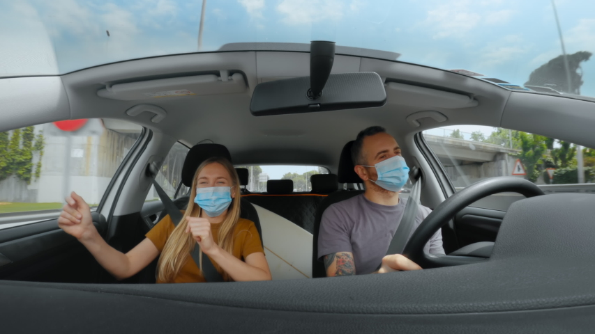 Happy young couple, friends finally go on vacation after quarantine and lockdown due to corona virus. Excited dance inside car on road trip in new normal, in face masks. Safe staycation concept