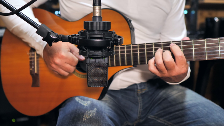 Static medium shot of a guitarist playing and recording a nylon string guitar with a pro condenser mic in a home recording studio.   Shutterstock HD Video #1055452742