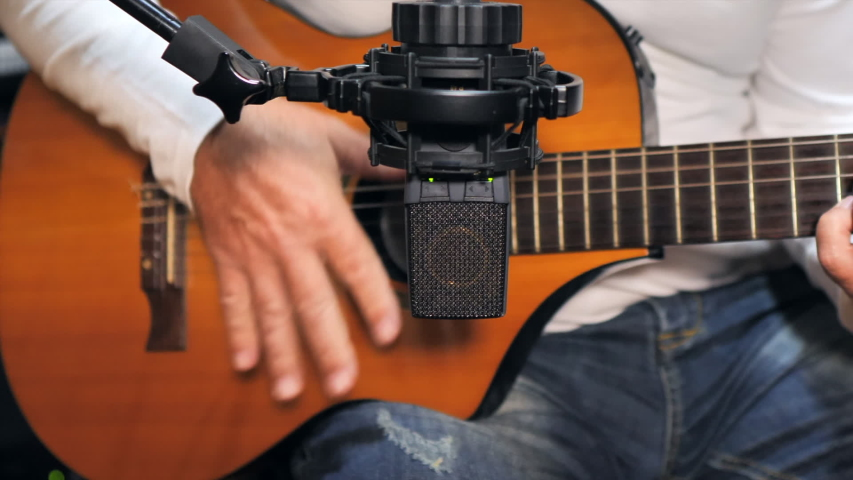 Close up shot of a guitarist playing and recording a nylon string guitar with a pro condenser mic in a home recording studio. Pan right   Shutterstock HD Video #1055452769