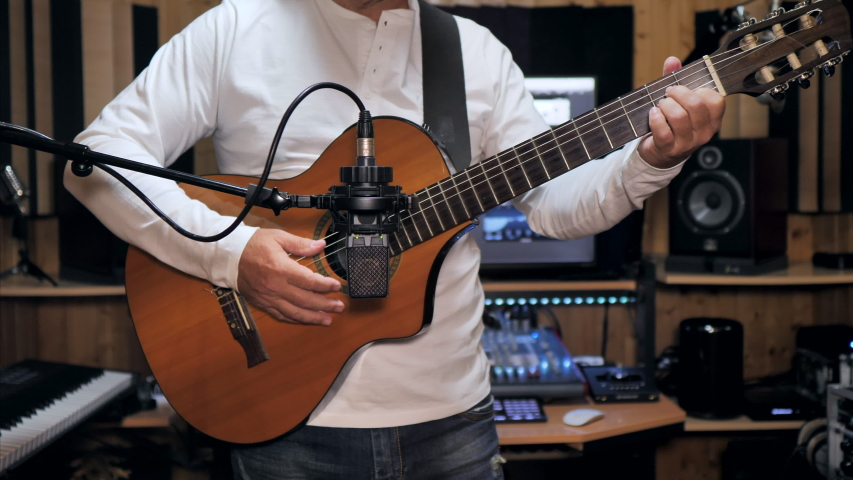 Static medium shot of a guitarist playing and recording a nylon string guitar with a pro condenser mic in a home recording studio.   Shutterstock HD Video #1055453687