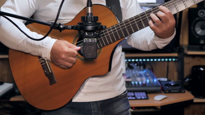 Static medium shot of a guitarist playing and recording a nylon string guitar with a pro condenser mic in a home recording studio. Zoom out   Shutterstock HD Video #1055455307