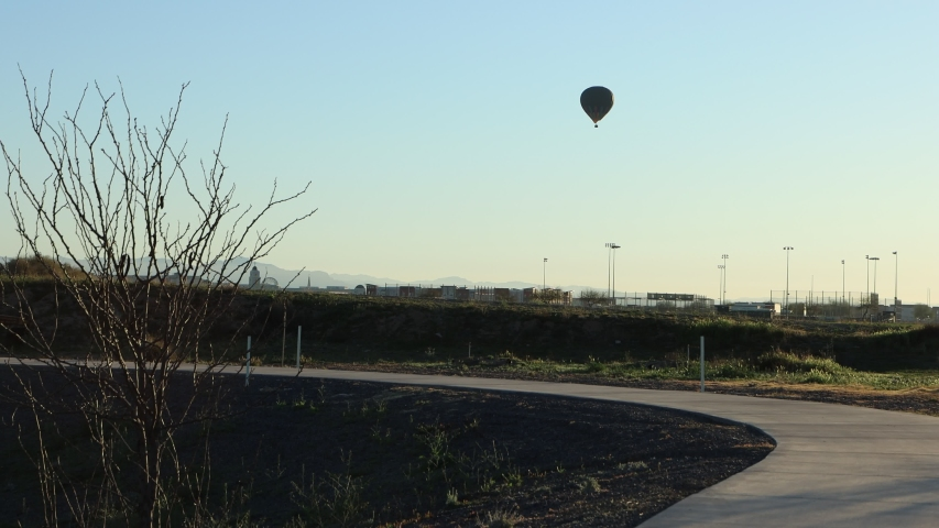 Backlit balloon flying over a city desert landscape foreground concrete walking trail in park | Shutterstock HD Video #1055474447