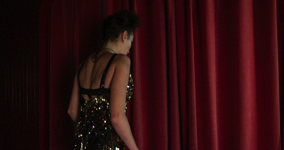 MS SLO MO Woman with luminescent plastic hoop walking out from behind curtain in cabaret at Soho / London, UK | Shutterstock HD Video #1055476919