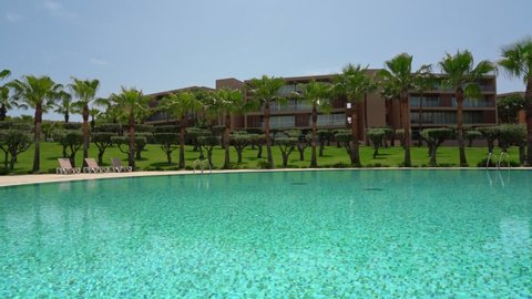 Luxurious, modern hotel in Salgados, Albufeira, Portugal. Beautiful park with palm trees and a pool.
