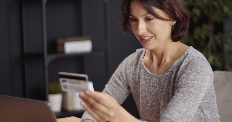 Smiling mature woman in domestic outfit holding credit card and typing all information on laptop for online purchases. Attractive lady ordering goods through internet while staying at home. Royalty-Free Stock Footage #1055485877