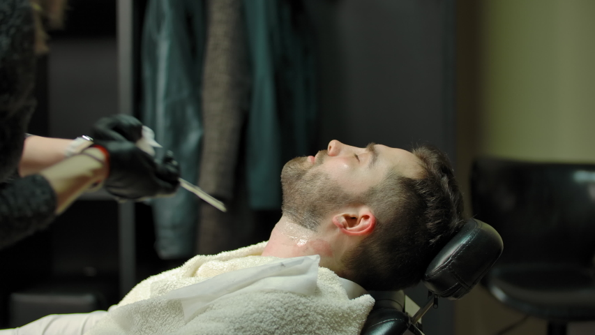 Blond woman in gloves using straight razor and tissue to shave beard of adult man with closed eyes during work in modern barbershop. | Shutterstock HD Video #1055489159