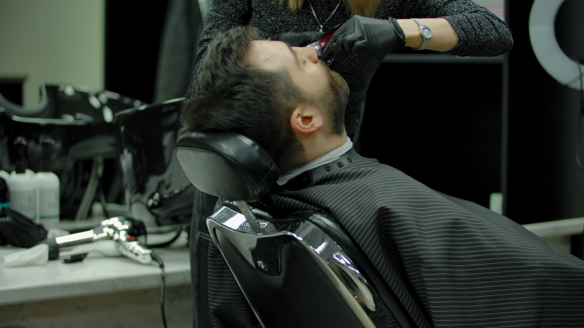 Tilt up view of blond woman in gloves using comb and electric razor to trim mustache of bearded male client during work in barbershop. | Shutterstock HD Video #1055489219