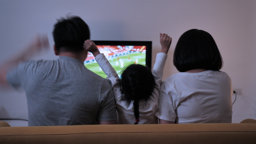 Rear view Asian family watching football championship on TV cheering having fun together in night shots. Entertainment in home Royalty-Free Stock Footage #1055489246