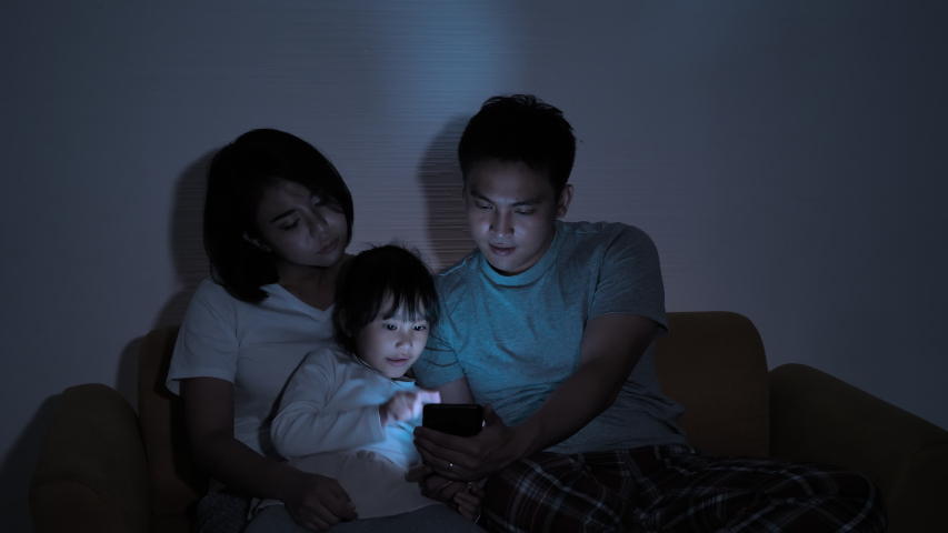 Asian family Father, mother and daughter spending time with mobile devices at home night shots. Connection, Communication, Entertainment, Fun from smartphone | Shutterstock HD Video #1055489258