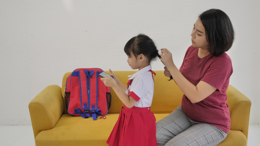 Happy Asian family Mother dressed daughter to go to school while using a mobile phone of Thai families in their daily life. | Shutterstock HD Video #1055489288