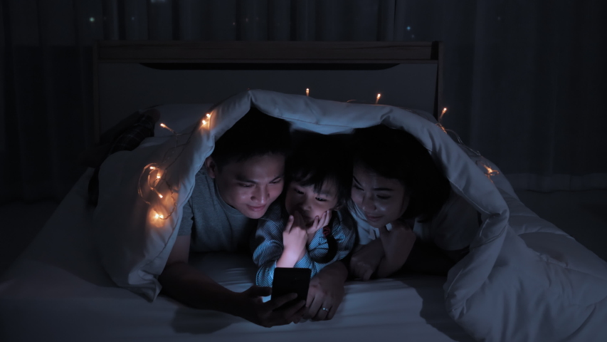Asian family Father, mother and daughter spending time with mobile devices on the bed under the blanket at home night shots. Connection, Communication, Entertainment, Fun from smartphone | Shutterstock HD Video #1055489312