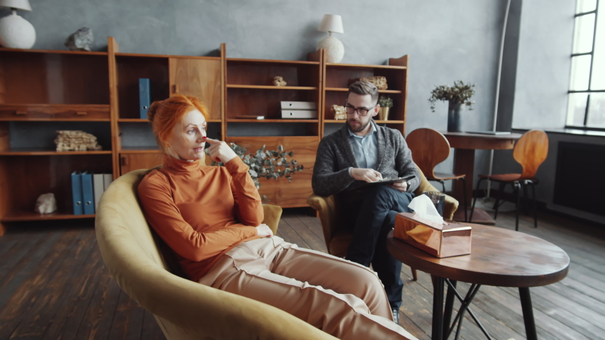Zoom in shot of depressed middle-aged redhead woman sitting on couch and complaining to professional male psychologist during consultation in counseling office | Shutterstock HD Video #1055489348