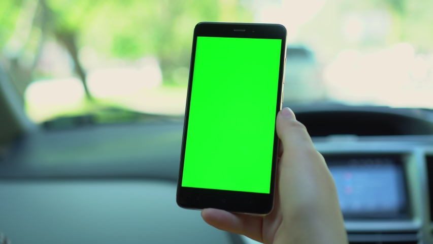 Close up of a woman's hand holding a mobile telephone with a vertical green screen in car chroma key smartphone technology cell phone street touch message display hand | Shutterstock HD Video #1055489699