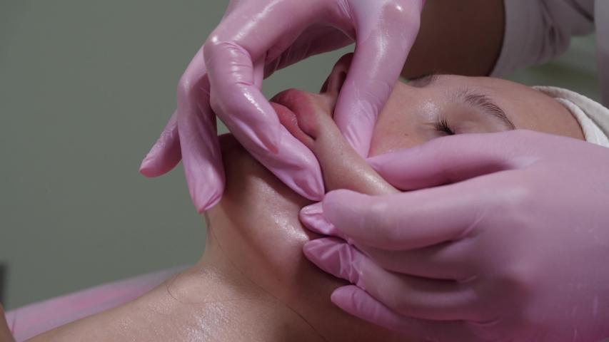 The procedure is a myofascial massage of the face closeup. Massage for facial skin rejuvenation. Lip and cheek massage. Buccal massage using Japanese technique | Shutterstock HD Video #1055489762