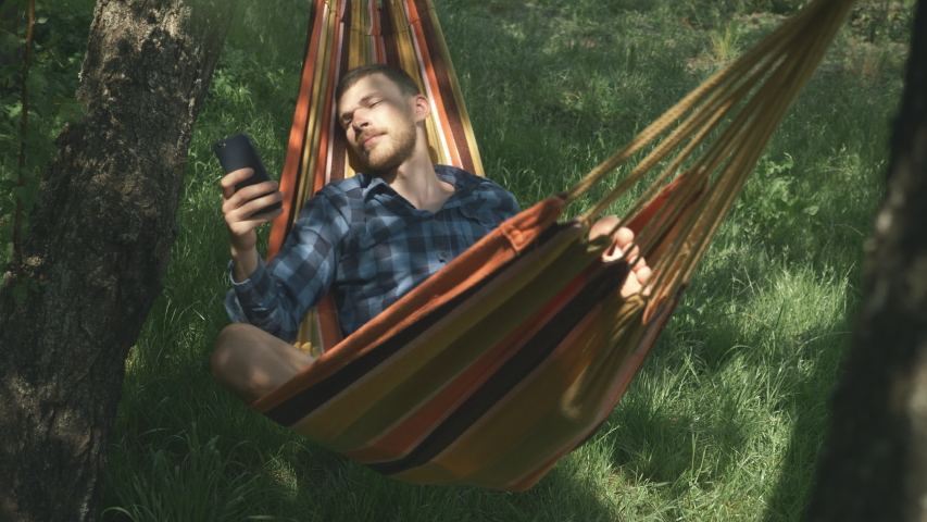 Mobile internet surfing. Man with cell phone in hands relaxing in hammock outdoors. Relax in hammock. Young male tourist lying on hammock and using mobile phone. Camping. Summer vacation | Shutterstock HD Video #1055489795