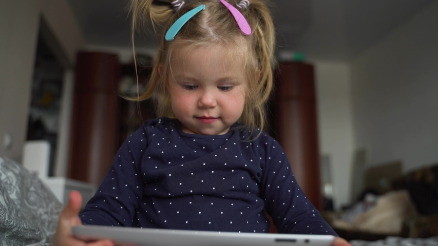 Curious cute preschool kid girl using digital tablet technology device lying on carpet floor alone. Small child hold pad computer surfing internet play game at home. Children tech addiction concept. | Shutterstock HD Video #1055491001