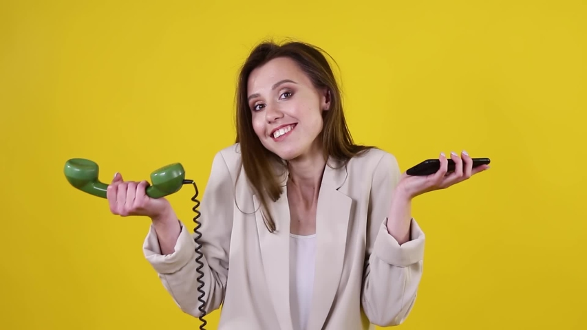 Brunette woman holding one green retro rotary telephone in one hand and a modern smartphone in the other. Girl holding old and new phone. Concept of technology progress | Shutterstock HD Video #1055491826