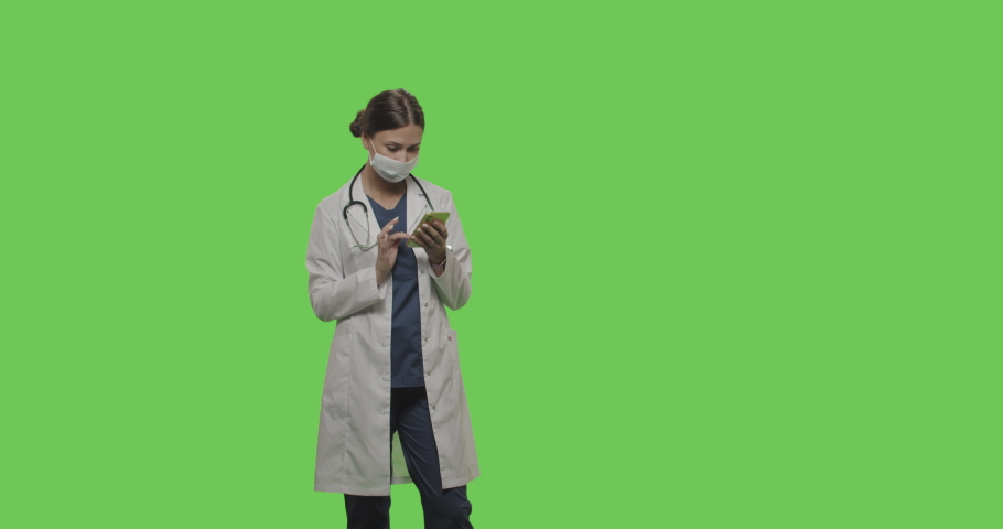 Portrait of female doctor using smartphone on green screen isolated with chroma key. Woman in facial mask standing and looking at camera smiling. 4K RAW graded footage | Shutterstock HD Video #1055492705