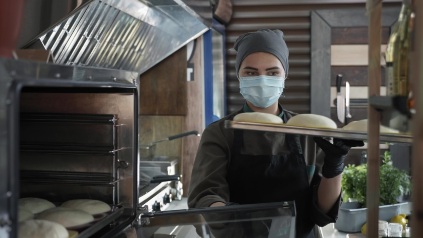 small business, young cute female baker in medical mask puts bake with slices of dough for baking in an electric furnace while working in bakery after removing quarantine